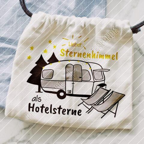 """Das Bild beinhaltet einen Stoffbeutel, auf dem sich ein Motiv der Plotterbande befindet. Das Design zeigt einen Wohnwagen, zwei Liegestühle und den Spruch """"Lieber Sternenhimmel als Hotelsterne""""."""