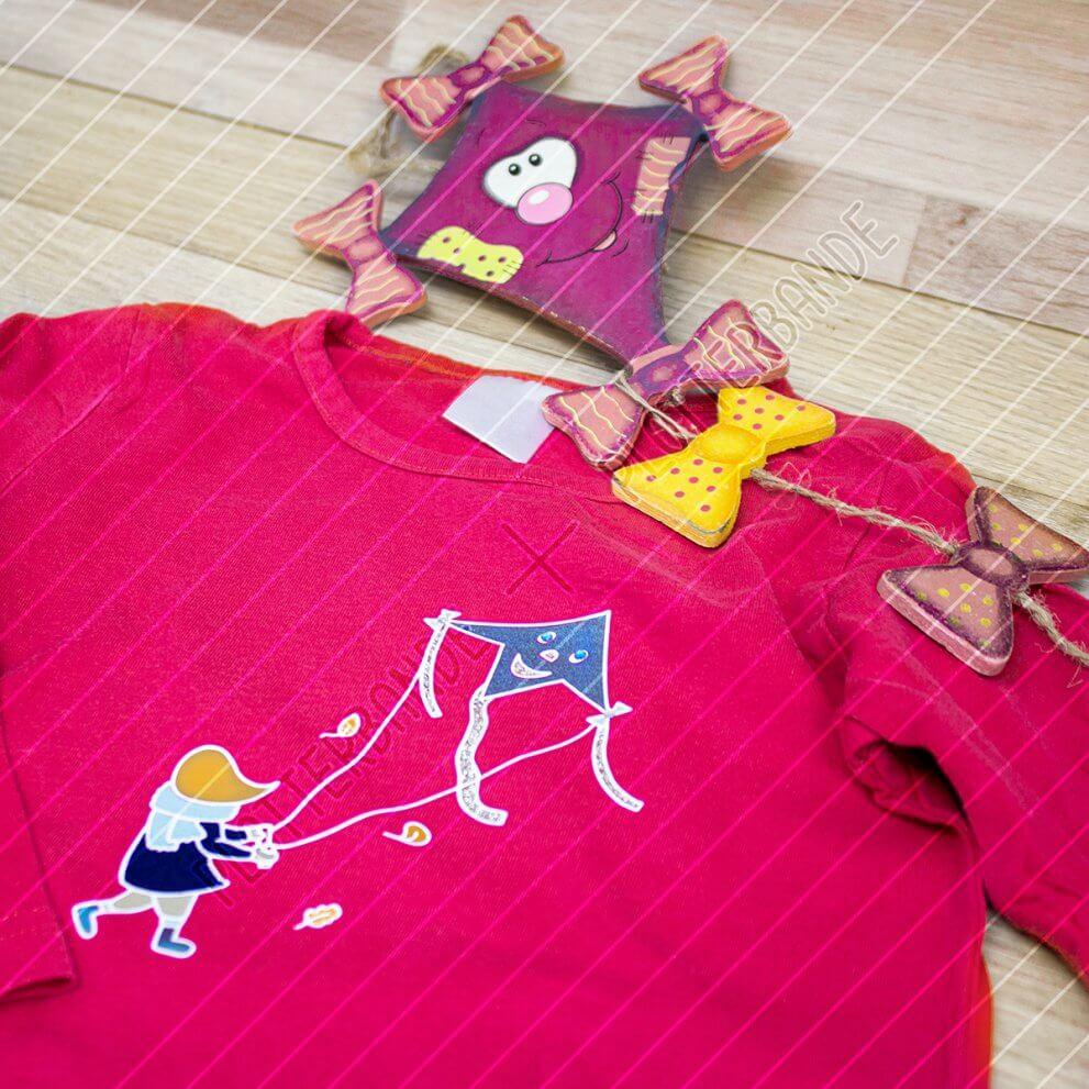 Ein pinker Pullover liegt auf einer Holzfläche neben einem Deko-Drachen. Darauf befindet sich das Drachensteigen-Design der Plotterbande.