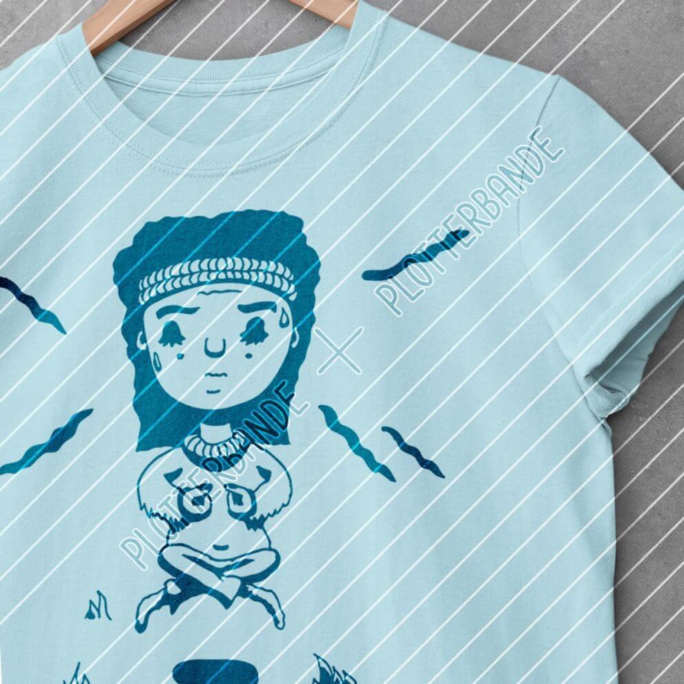 Ein hellbalues Tshirt mit dem Yogalady-Design der Plotterbande liegt auf einer Betonfläche.