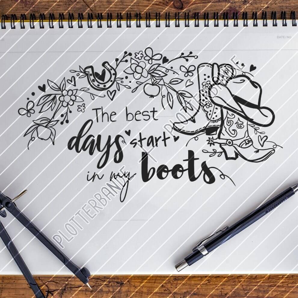 Das Bild zeigt einen Zeichenblock auf dem sich ein Motiv mit Westernstiefel und den Spruch the best days start in my boots der Plotterbande befindet. Daneben liegt ein Stift und ein Zirkel.