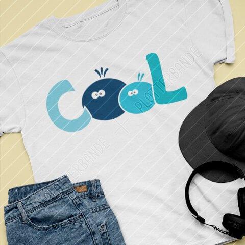 """Man sieht ein Set Kinderkleidung neben einer Cap und Kopfhörern. Das T-Shirt trägt das """"Cool""""-Design der Plotterbande."""