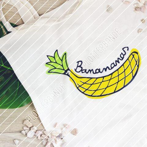 Auf einem Holzboden liegt ein weißer Beutel mit dem Banananas-Design der Plotterbande – eine Illustration, die Elemente einer Banane und einer Ananas verbindet.