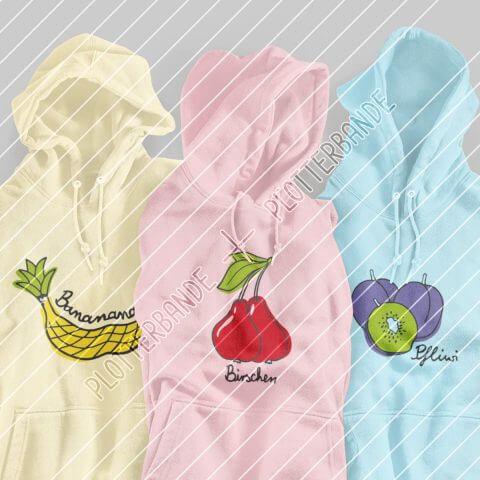 Auf dem Bild sieht man drei farbige Pullover mit dem jeweiligen Aufdruck des Plotterbande-Designs Bananas, Birschen und Pfliwi.