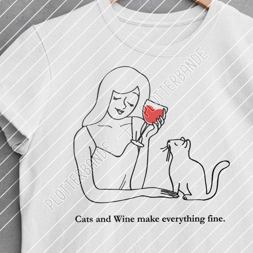 Ein weißes Shirt mit dem Cats-and-Wine-Design der Plotterbande liegt auf einer Betonfläche.