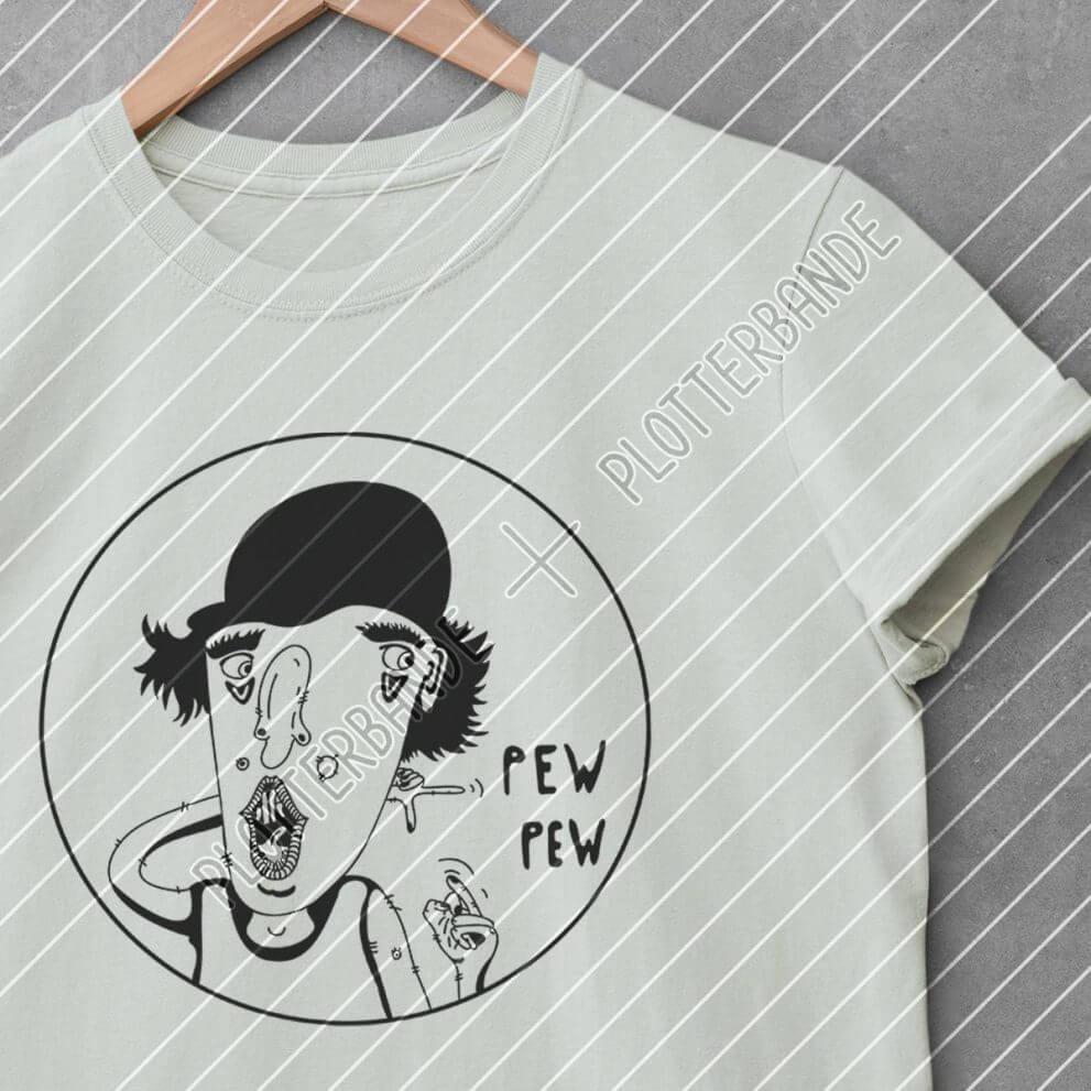 Ein menthol farbiges T-Shirt liegt auf einer Betonfläche. Darauf gedruckt ist das Cooler Dude-Design der Plotterbande.