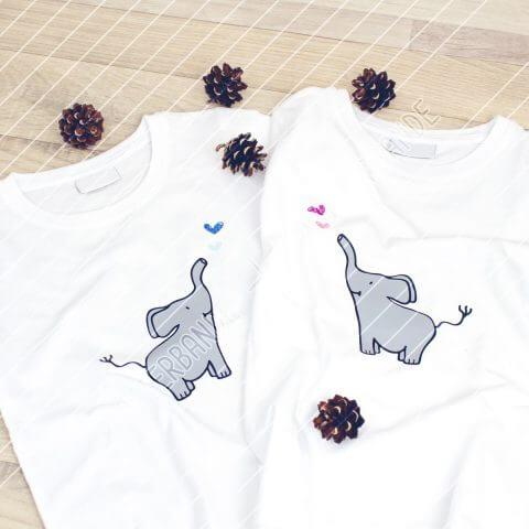 Zwei weiße Kinderhirts liegen auf einer Holzfläche. Beide tragen das Elefant-mit-Herz-Design der Plotterbande – einmal mit blauen und einmal mit rosa Herzen.