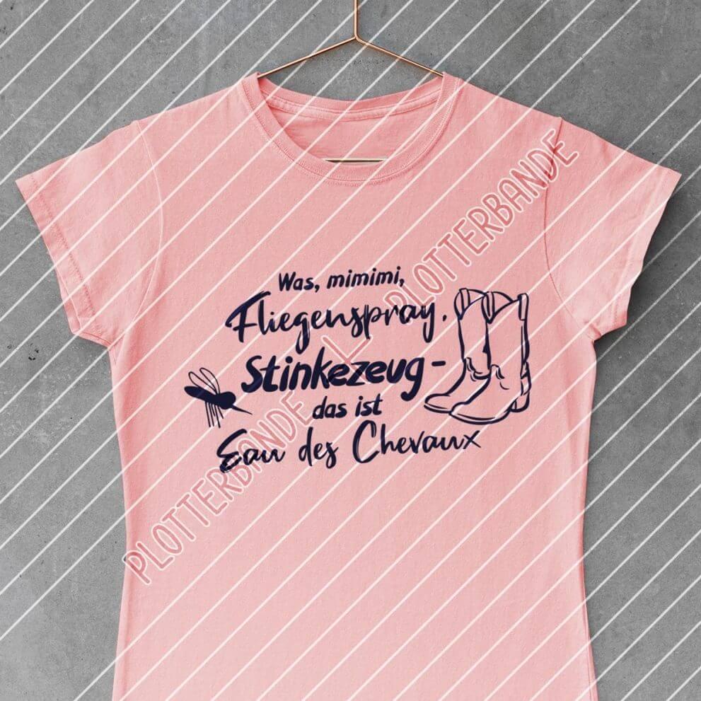 Ein pinkes T-Shirt mit dem Fliegenspray-Design der Plotterbande liegt auf einer Betonoberfläche.