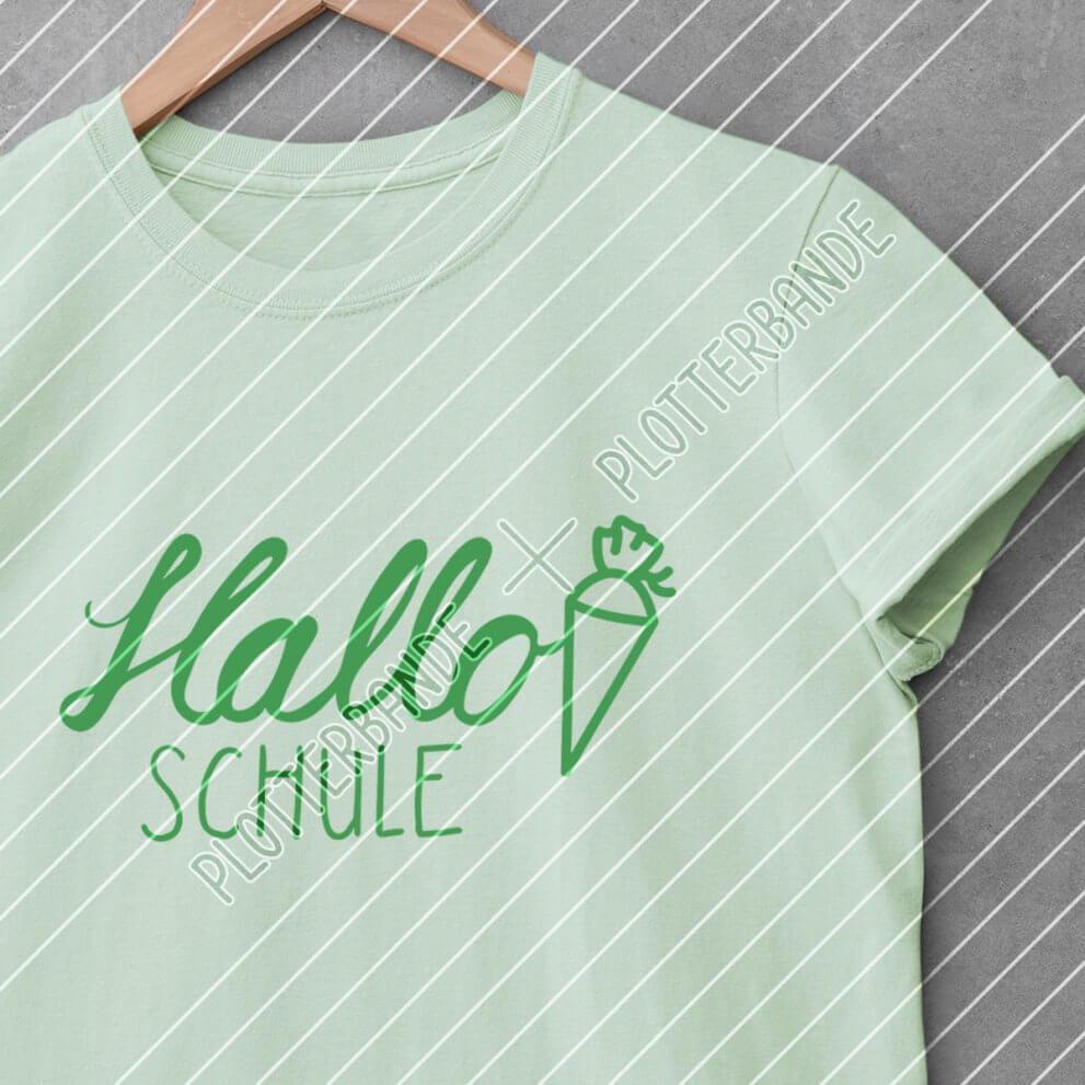 Ein grünes T-Shirt liegt auf einer Betonfläche. Darauf gedruckt ist das Hallo Schule-Design der Plotterbande.