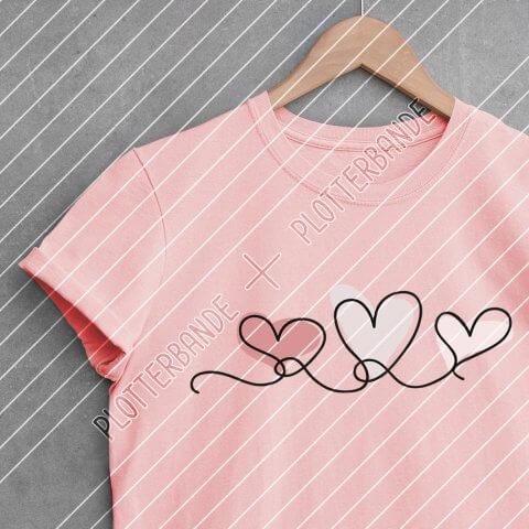 """Ein pinkes T-Shirt mit dem Plotterbande-Design """"Herzenslinie"""" liegt auf einer Betonoberfläche."""