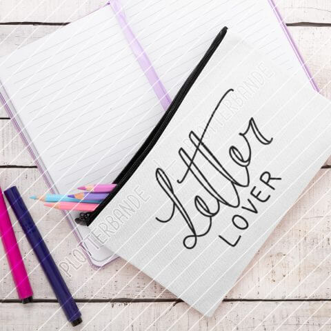 Das Bild zeigt ein weißes Federmäppchen, aus dem Stifte kullern. Das Letter Lover-Design der Plotterbande ist auf das Mäppchen gedruckt.