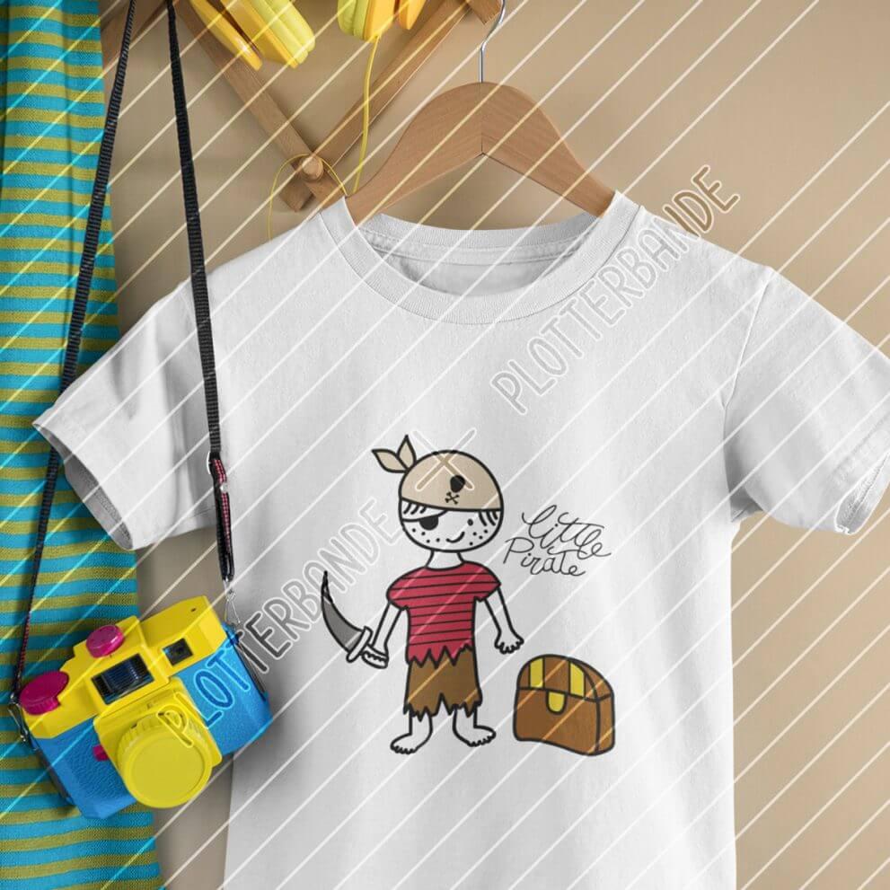 An einem Kleiderbügel hängt ein weißes T-Shirt mit dem Kleiner Pirat-Design der Plotterbande. Die Illustration zeigt einen Jungen in Seeräuber-Montur mit Augenklappe, Krummsäbel und Schatztruhe.