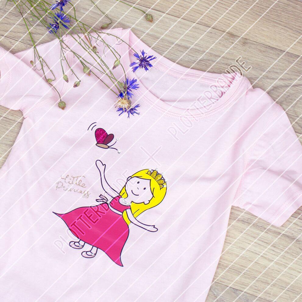 Auf einer Holzfläche liegt ein rosa T-Shirt mit dem Kleine Prinzessin-Design der Plotterbande.