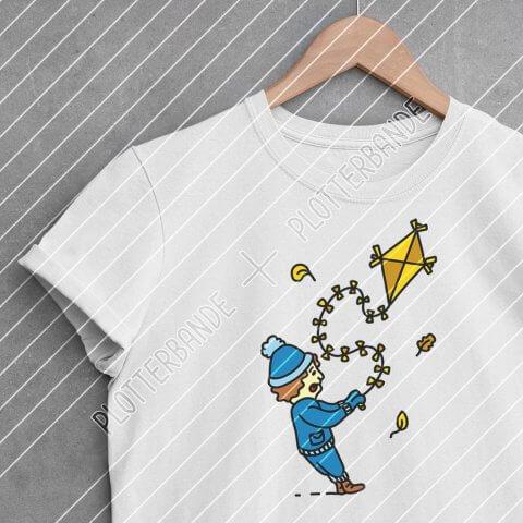 Ein weißes T-Shirt hängt auf einem Kleiderbügel. Darauf ist das Drachsteigen-Design der Plotterbande zu sehen.