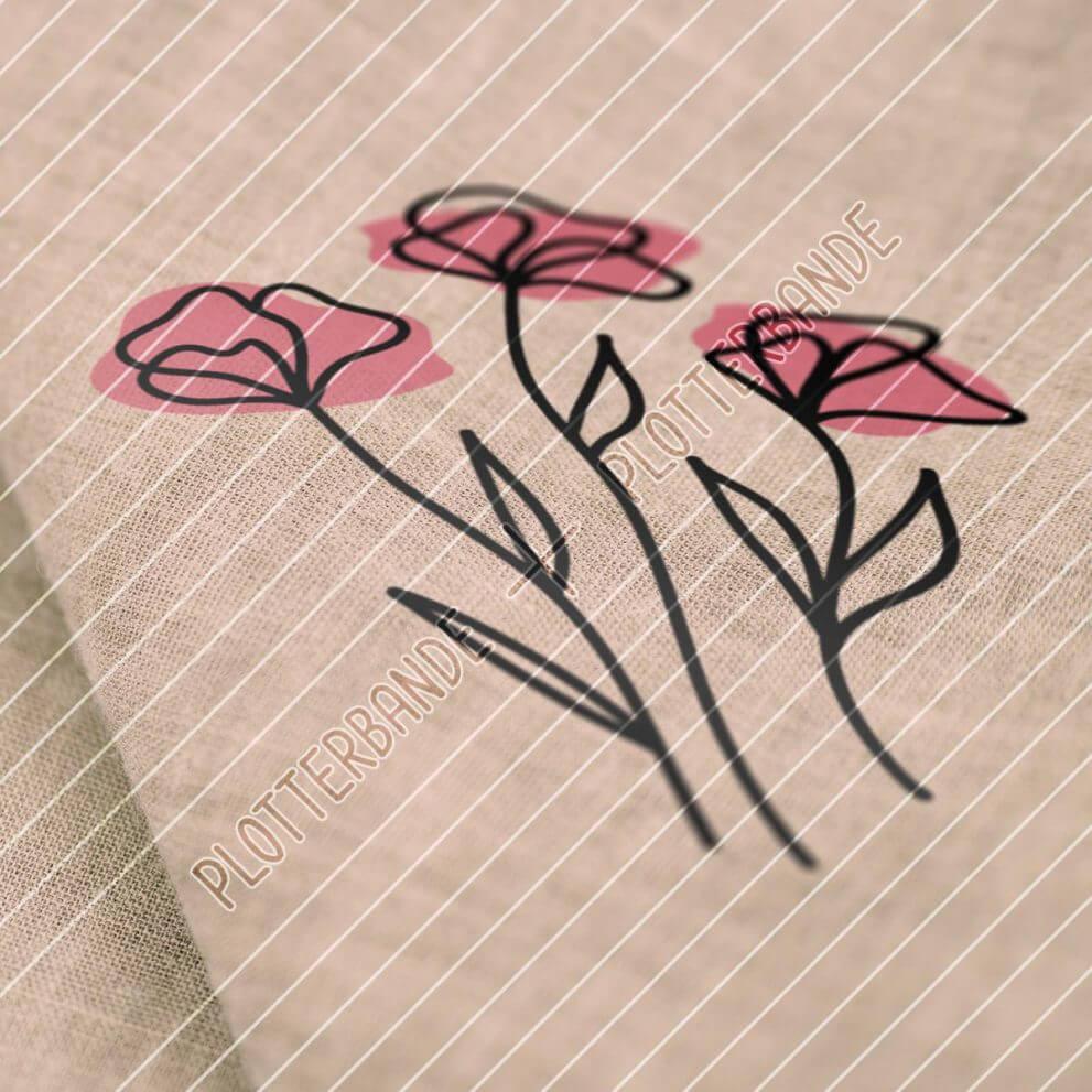 Das Bild zeigt einen Stoff, auf dem ein Plottdesign der Plotterbande gedruckt ist. Das Design zeigt drei Mohnblumen mit jeweils einem Farbakzent.