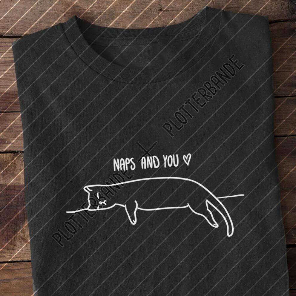 """Ein schwarzes T-Shirt mit dem Plotterbande-Design """"Naps and You"""" liegt auf einer Holzfläche."""
