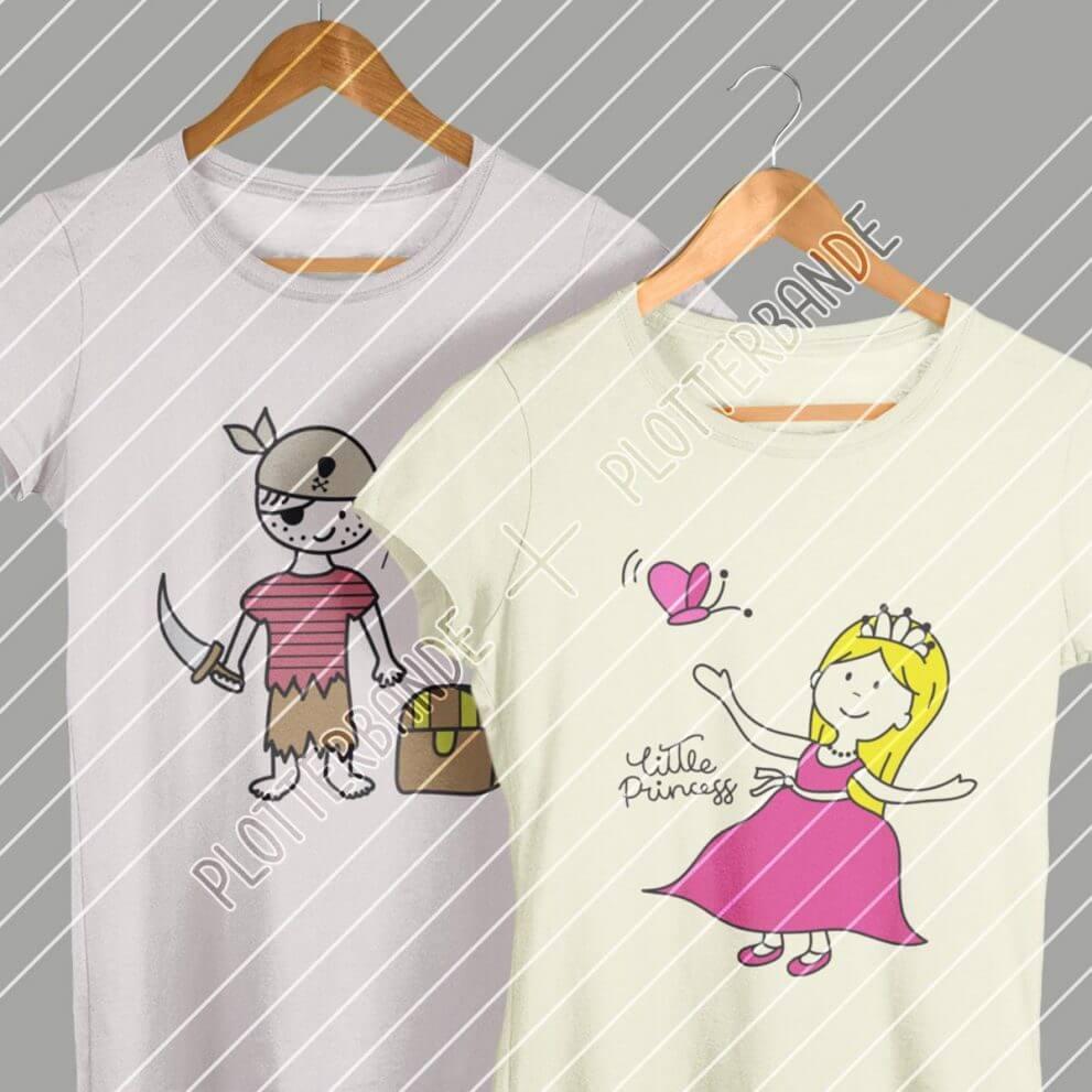 """Zwei T-Shirts hängen vor einer grauen Wand. Auf dem einen T-Shirt ist das Plotterbande-Design """"Kleiner Pirat"""" und auf dem anderen """"kleine Prinzessin"""" bedruckt."""