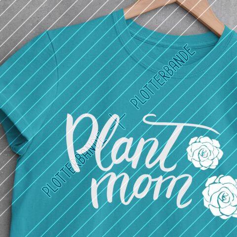 """Ein hellblaues T-Shirt mit dem Plotterbande-Design """"Plant Mom"""" liegt auf einer Betonoberfläche."""