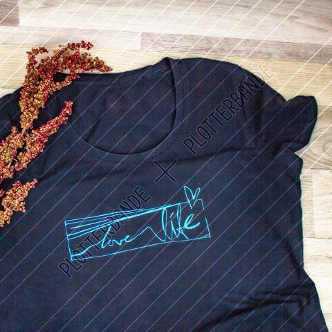 Auf einer Holzfläche liegt ein blaues T-Shirt mit dem Love Life-Design der Plotterbande .