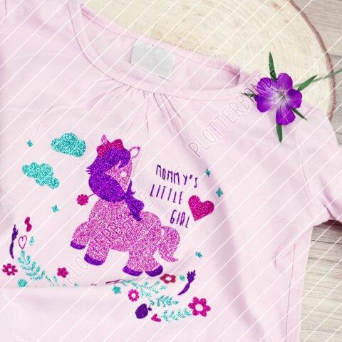Ein rosa Kindershirt liegt auf einer Holzfläche. Darauf ist das Babyhorse-Design der Plotterbande in Glitzerfarben zu sehen.
