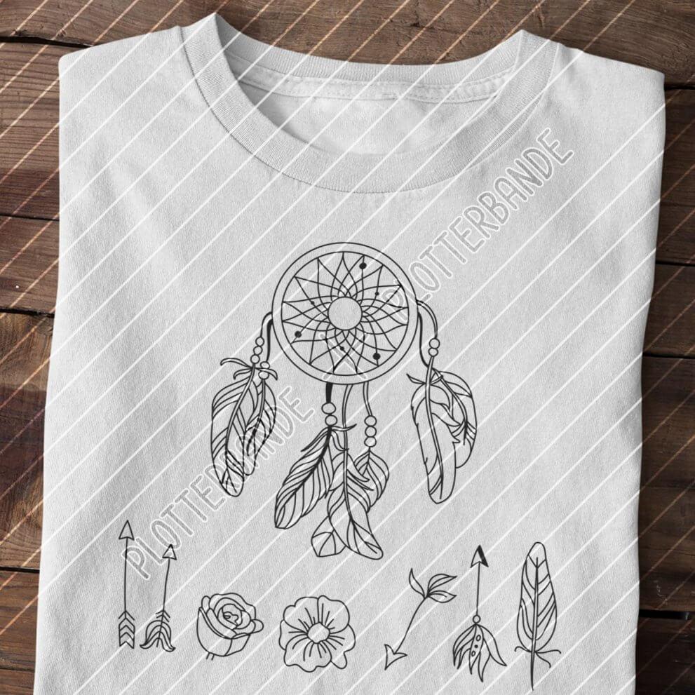 Auf einer Holzfläche liegt ein hellgraues T-Shirt mit dem Boho-Traumfänger-Design der Plotterbande.