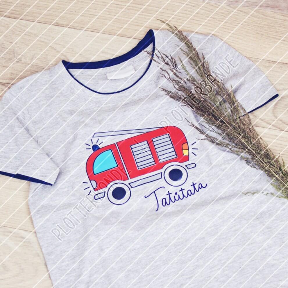 """Ein hellblaues T-Shirt liegt auf einer Holzfläche. Darauf ist das Design """"Kleiner Feuerwehrmann"""" der Plotterbande zu sehen."""