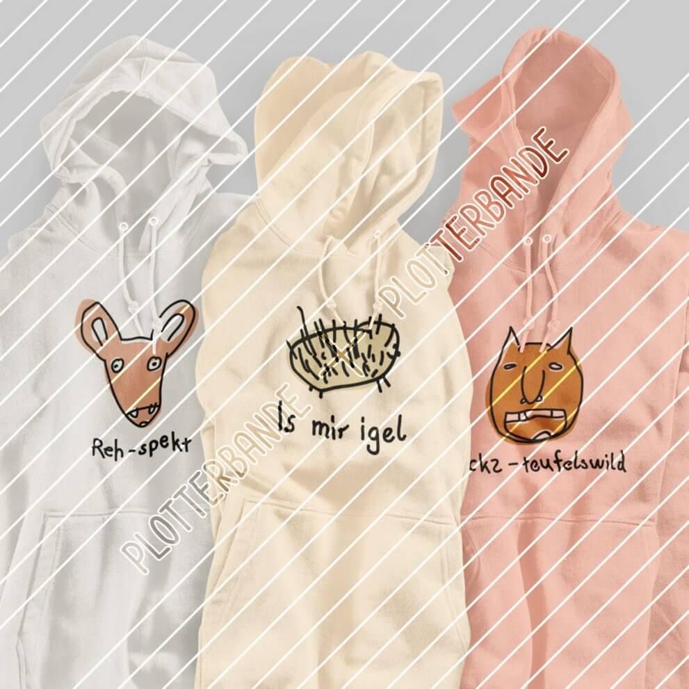 """Drei weiße Pullover hängen auf Kleiderbügeln im Schrank. Auf jedem ist eins der """"Statement-Waldtiere"""" Plottdesigns der Plotterbande zu sehen."""