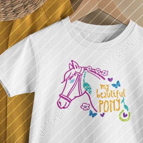 """Das Bild zeigt ein weißes T-Shirt auf einem Kleiderbügel. Darauf ist das """"My beautiful Pony"""" Plottdesign der Plotterbande mit bunten Outlines."""