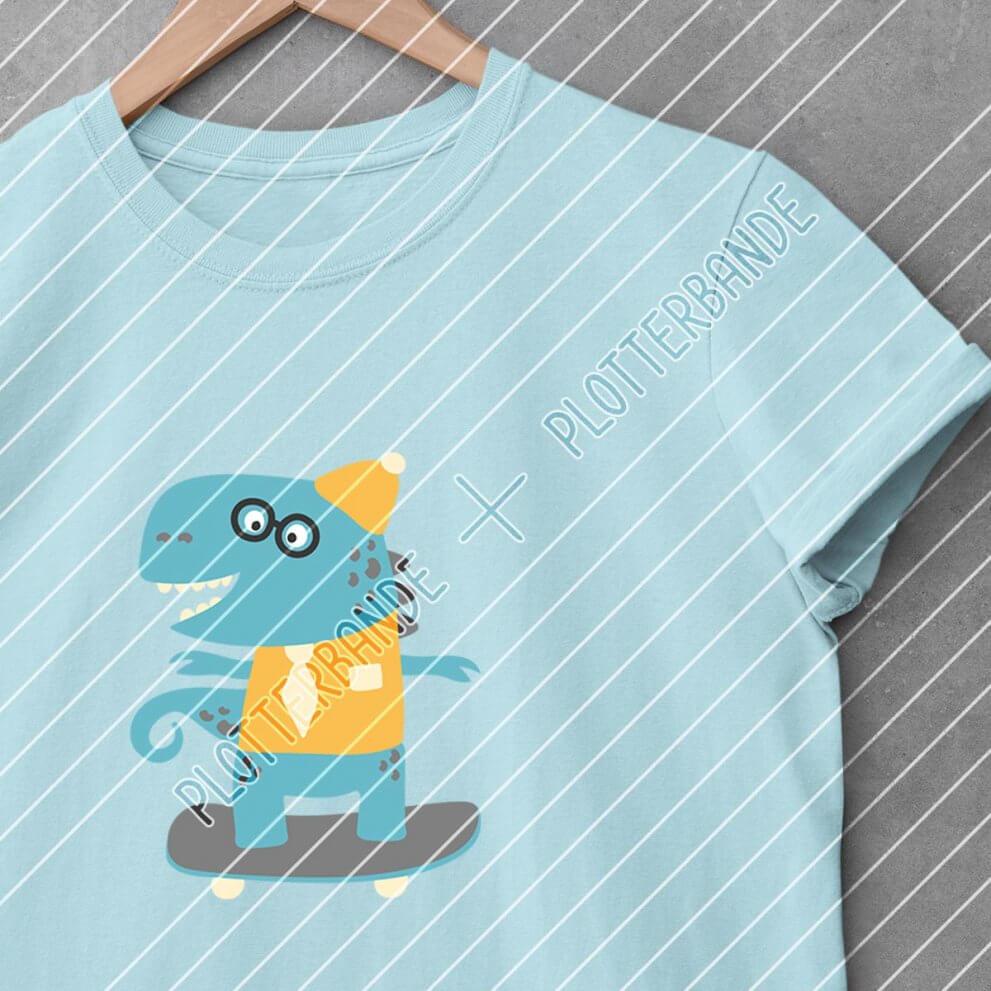 Ein blaues T-Shirt hängt auf einem Kleiderbügel. Darauf zu sehen ist das Skater-Dino-Plottdesign der Plotterbande