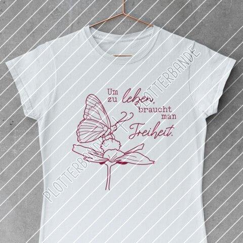 """Ein weißes T-Shirt hängt auf einem Kleiderbügel. Darauf zu sehen ist das """"Leben Freiheit"""" Design der Plotterbande mit lila Outlines."""