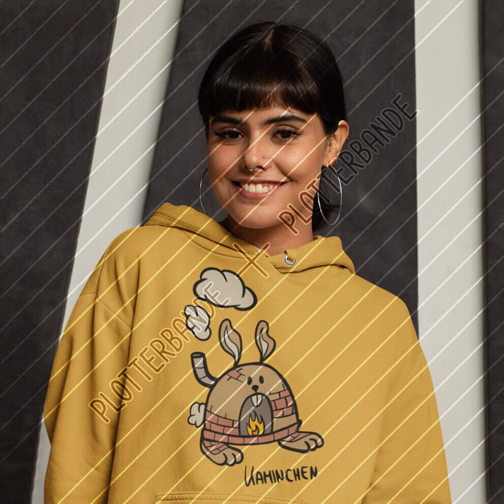 Eine junge Frau trägt einen gelben Kapuzenpullover mit dem Kaminchen-Design der Plotterbande.