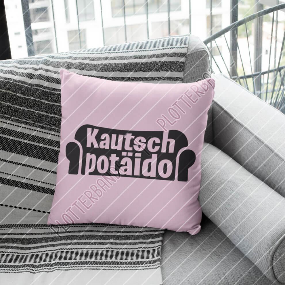 """Ein rosa Kissen liegt auf einer Couch. Es trägt das Plottdesign """"Kautschpotäido"""" der Plotterbande."""