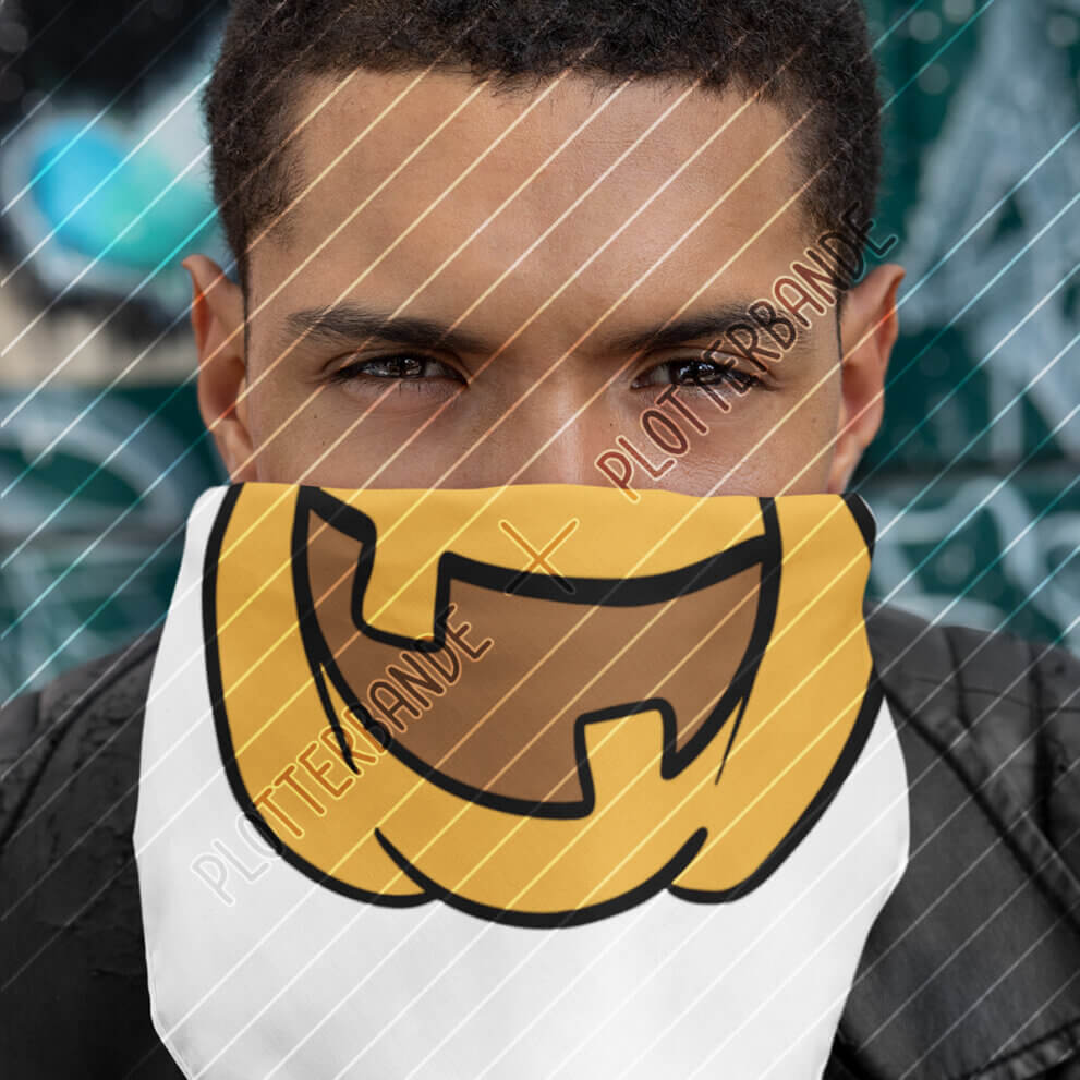 Ein junger Mann hält sich ein weißes Tuch vors Gesicht. Auf dem Tuch ist das Halloween-Kürbislachen-Design der Plotterbande abgebildet.