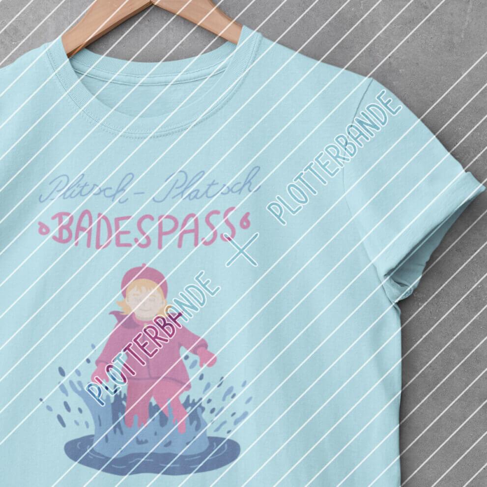 An einem Kleiderbügel hängt ein blaues T-Shirt, auf welches das Plitsch-Platsch-Design der Plotterbande gedruckt ist.