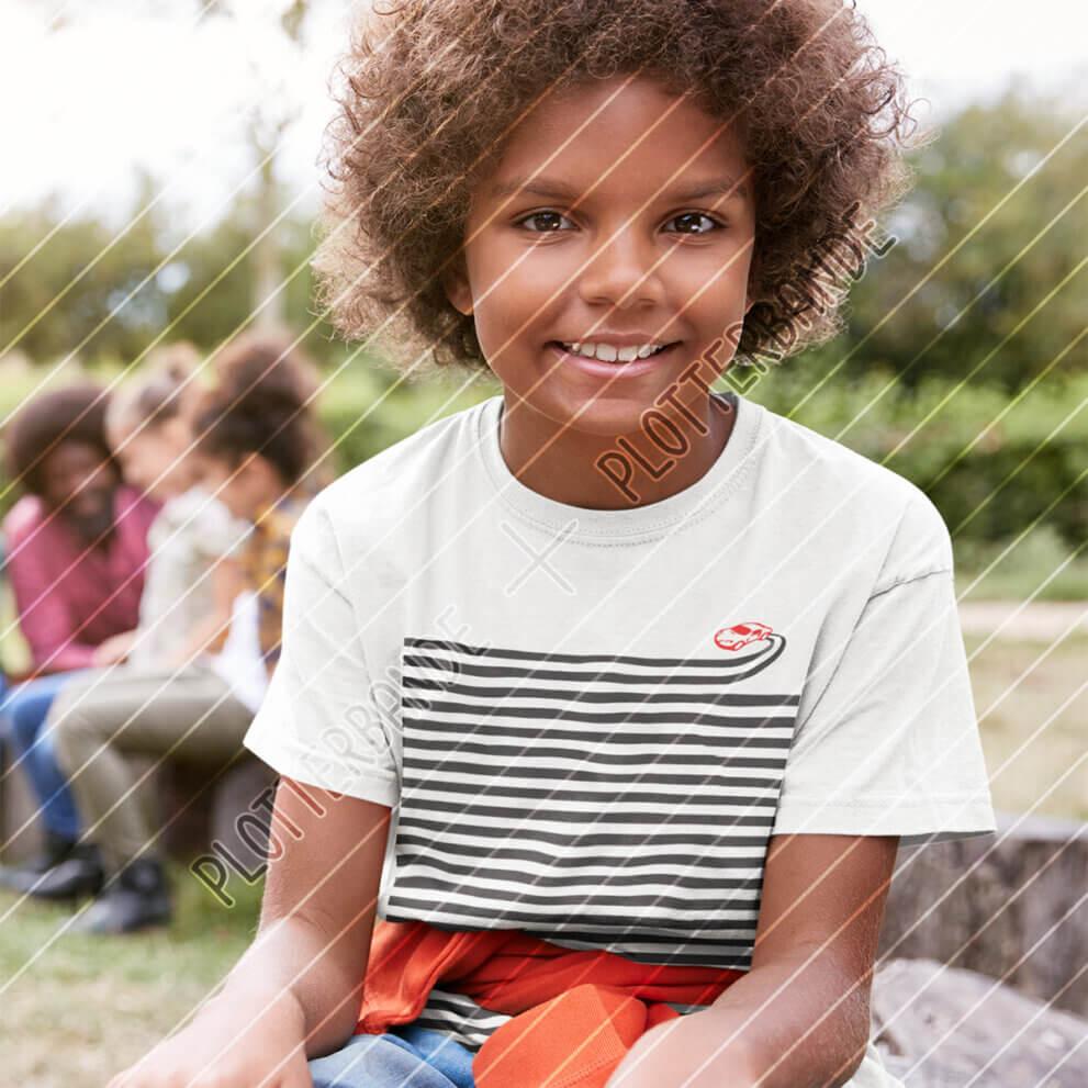 Ein Junge lächelt in die Kamera und trägt ein weißes Shirt mit dem Wenn-sich-zwei-Streifen-Drift-Plottdesign der Plotterbande.