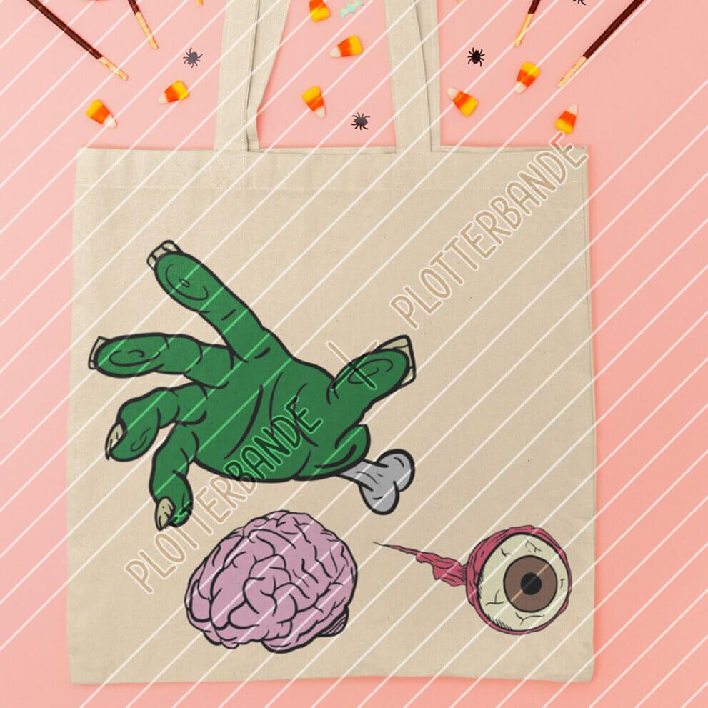 Auf einer Einkaufstasche ist das Halloween-Zombiehand-Design der Plotterbande abgebildet.