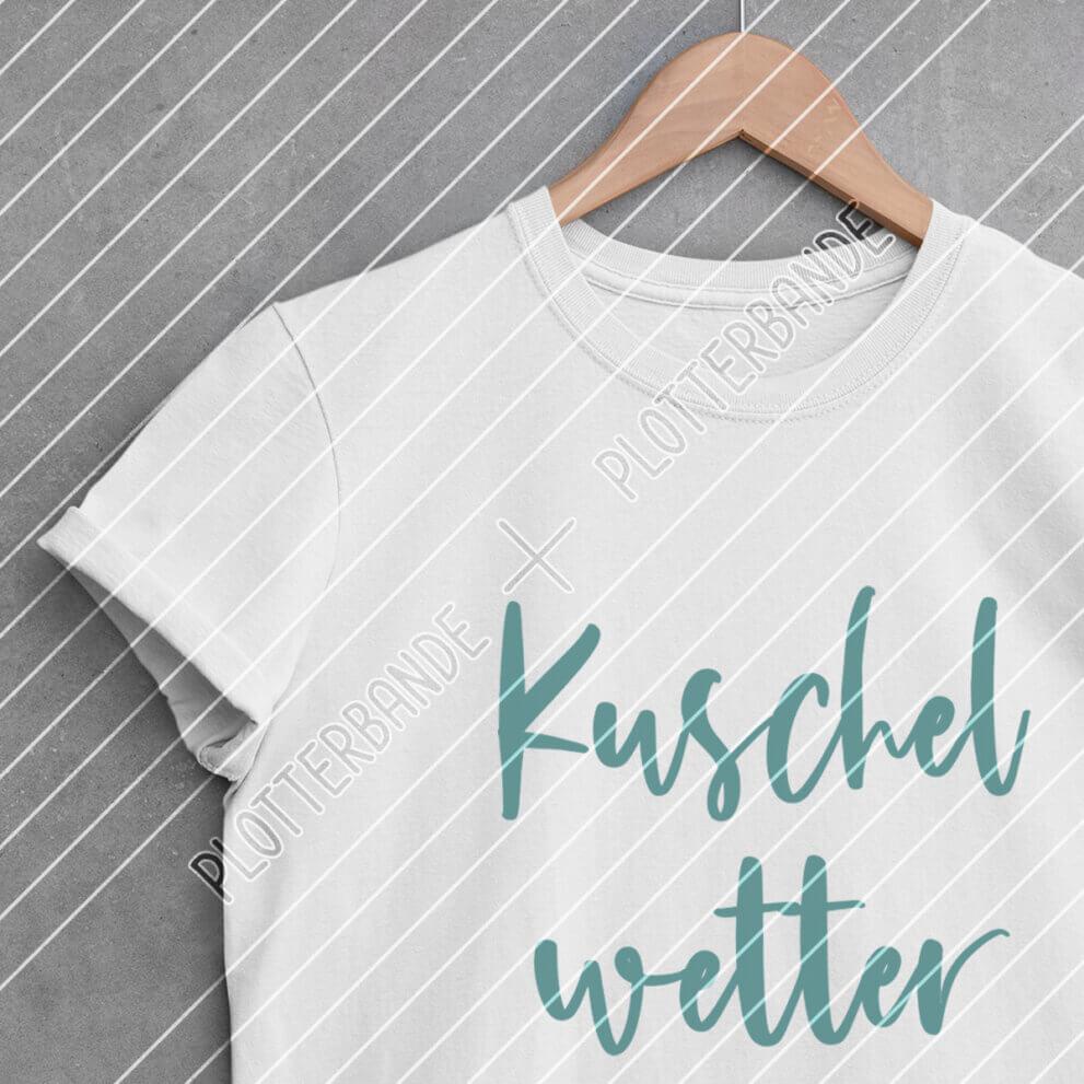 Ein weißes T-Shirt hängt auf einem Kleiderbügel. Darauf zu sehen ist das Kuschelwetter-Plottdesign der Plotterbande in blauer Schrift.
