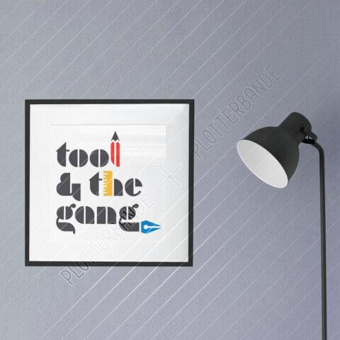 Ein Bild mit schwarzem Bilderrahmen hängt an einer grau-blauen Wand. Darauf zu sehen ist das Tool-and-the-Gang-Plottdesign der Plotterbande.