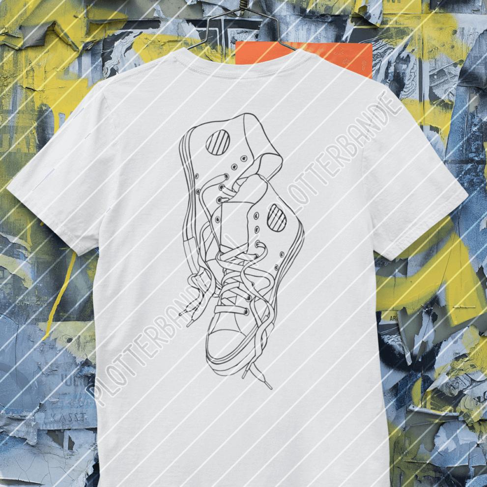 (3) An einem Kleiderbügel hängt ein weißes T-Shirt mit dem Sneaker-Design der Plotterbande.