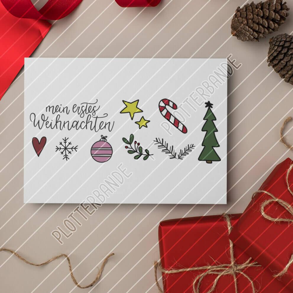 Auf einer weihnachtlich dekorierten Fläche liegt eine Karte mit dem Mein erstes Weihnachten-Design der Plotterbande.