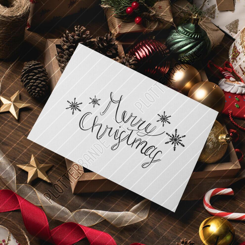 Ein weiße Karte liegt auf einem weihnachtlich dekorierten Tisch. Auf die Karte ist das Merry Christmas-Design der Plotterbande gedruckt.