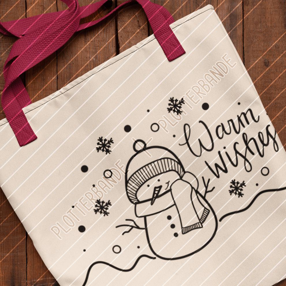 (1) Auf einer Holzfläche liegt eine weiße Tasche mit dem Schneemann-Design der Plotterbande.