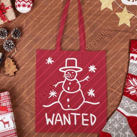 (1) Auf einer Holzfläche liegt eine rote Tasche mit dem Schneemann Wanted-Design der Plotterbande.