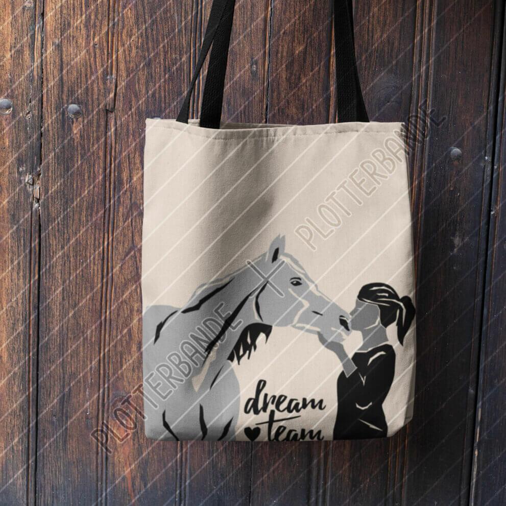 Eine weiße Stofftasche hängt an einem Holzzaun. Auf ihr zu sehen ist das Dreamteam-Design der Plotterbande.