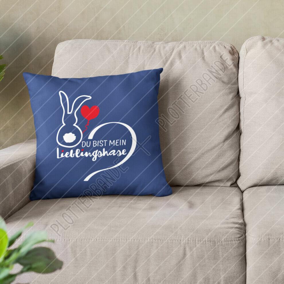 Ein blaues Kissen liegt auf einer Couch. Darauf zu sehen ist das Lieblingshase-Design der Plotterbande.