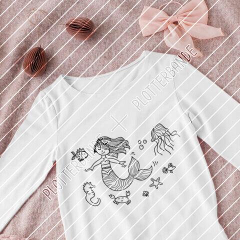 (1) Man sieht ein weißes T-Shirt auf einer rosa Decke. Auf dem Shirt ist das Meerjungfrau-Design der Plotterbande abgebildet.