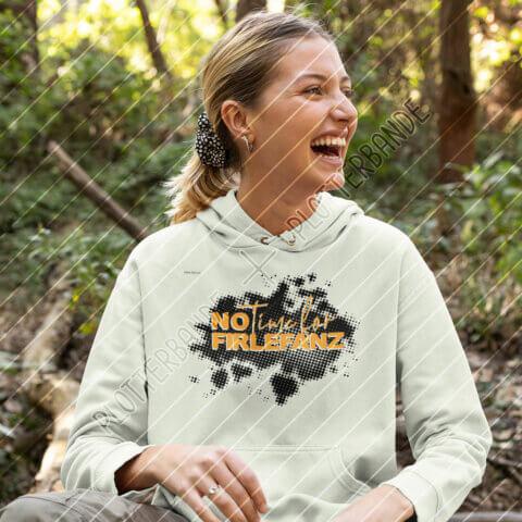 Eine junge Frau sitzt vor einem Waldhintergrund und lacht. Sie trägt einen grünen Pullover mit dem No-time-for-Firlefanz-Design der Plotterbande.