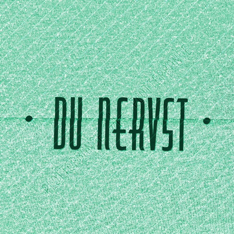 (1) Das Bild zeigt einen grünen Stoff mit dem Geheimschrift-Du-nervst-Design der Plotterbande.